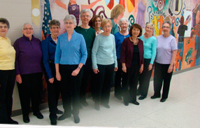 Group of women stand and smile for camera in front of a mural