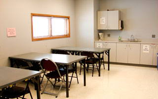 Arts and Crafts Room features tiled floor and a sink, folding tables and chairs