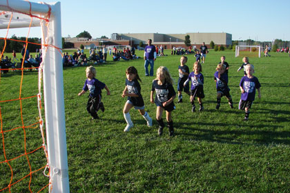 Children sprint towards soccer goal while crowd watches in background