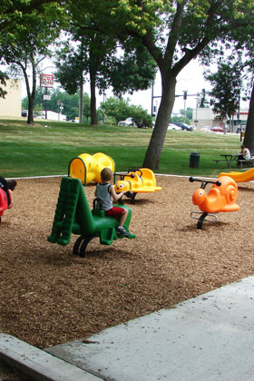 Young child rides a green toy at Moats Park with other toys in the background