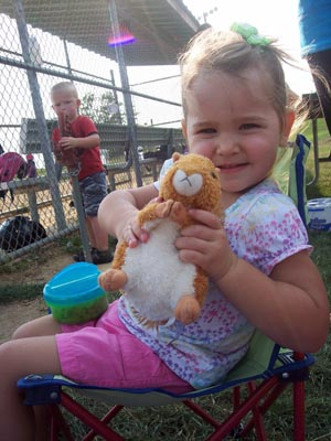 Girl holds scooter doll during baseball game