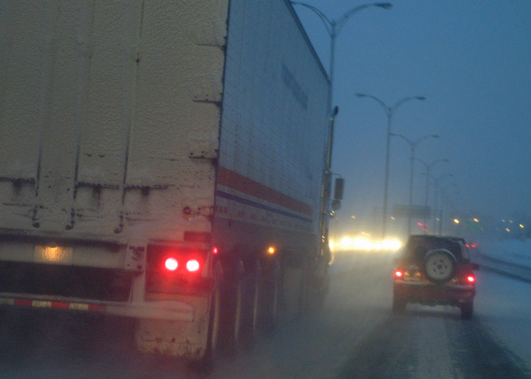 Rear-view of a semi-truck passing a car at dusk on a busy freeway Rear-view of a semi-truck passing a car during a winter storm at dusk on a busy freeway