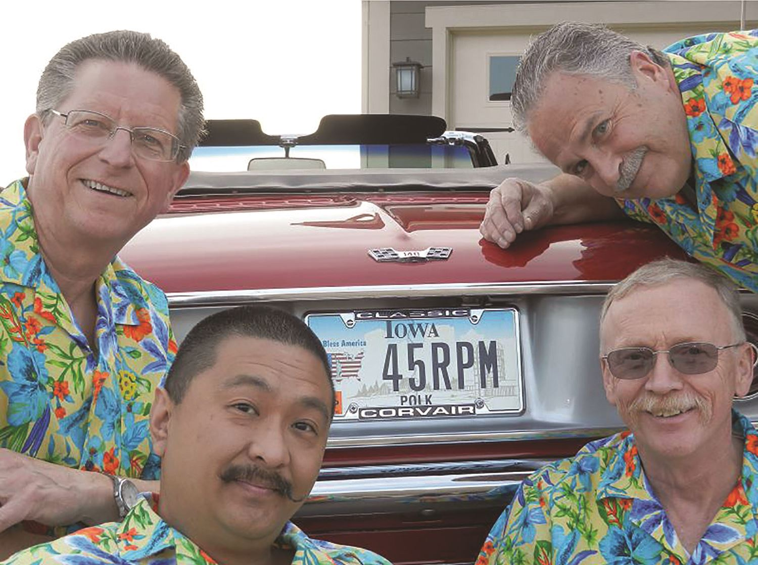 A quartet of similing singers in Hawaiian shirts surround a classic car
