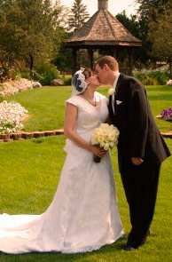 A newly wedded couple kisses on a grassy knoll with the Buxton Gazebo in the background